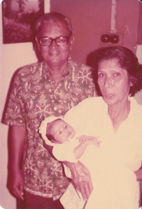 My grandmother Patsy Sequeira (making one of her funny faces) and grandfather Cyril Pinto, and me (in a funny hat thing), at my Baptism.